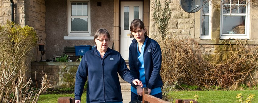 Community nurses, leaving a house through garden gate
