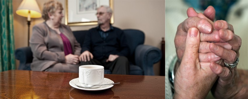 Ederly couple sitting on couch in background, tea cup on table in foreground / close up of holding hands