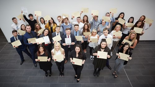 modern apprencticeship graduates posing with certificates to celebrate