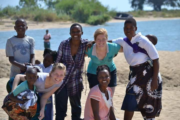 Group photo. Becky Dunphy and sister Naomi in Malawi with a group of boys and girls